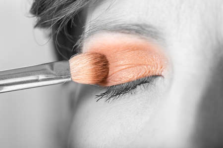 brush in: Applying eyeshadow to an eyelid using a small cosmetic brush in a beauty concept with selective color in a greyscale image. Stock Photo