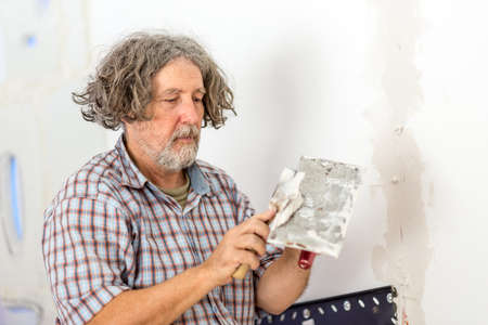 homeowner: Middle-aged male builder or homeowner repairing a wall applying filler plaster from a small board with a scraper as he repairs a crack or opening.