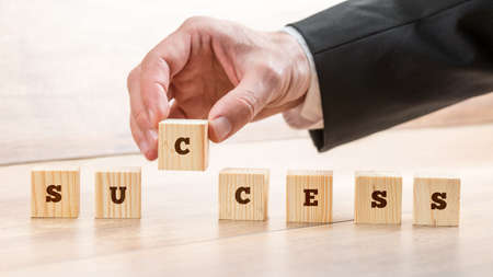 building blocks business: Close up Hand of a Businessman Arranging Small Wooden Blocks on the Table for Success Concept. Stock Photo