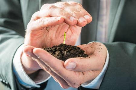 Бизнесмен держит саженец прорастания в плодородной земле обхватил в ладони в концептуальные изображения экологического сознания или бизнес запуске.