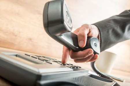 dialing: Hand of a businessman with dark gray suit holding the receiver of a black corded desk phone while dialing, in the office.