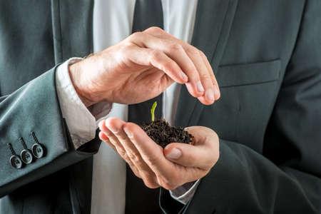 compromiso: Empresario alimentar una planta de semillero en germinación en suelo fértil y abonado ventosas en la mano, mientras que lo cubre con la otra conceptual de la conciencia de la conservación del planeta.