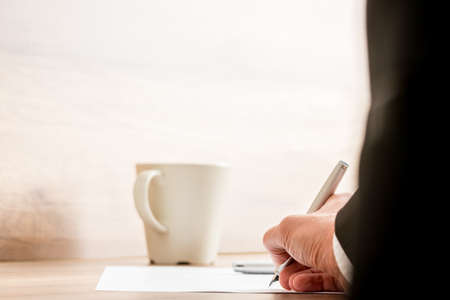 Businessman signing a document or contract with a mug of coffee standing on the desk, low angle view between his arm of the paperwork. Stock Photo