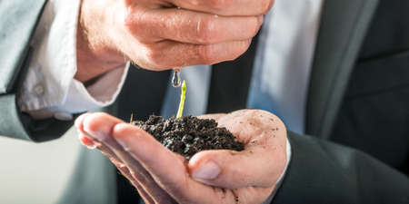 environmental awareness: Businessman holding a sprouting seedling in fertile earth cupped in the palm of his hand watering it with the other in a conceptual image of environmental awareness.