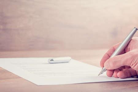 firmando: Imagen de estilo retro de la firma del contrato la mano de negocios u otros documentos importantes en un escritorio de madera rústica.