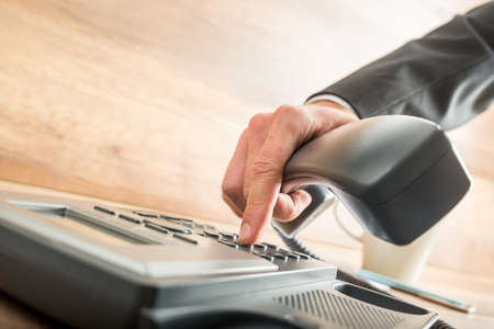 landline: Consultant holding the receiver of a corded desk phone while dialing, in the office. Stock Photo