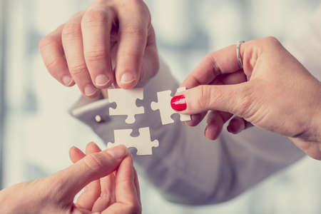 Hands of different people matching together three complementary puzzle pieces, concept of unity and problem solving, close-up with retro filter effect.