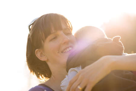 maternal: Happy young  protective mother lovingly cuddling her baby boy to her shoulder with maternal smile backlit by a bright sunburst.