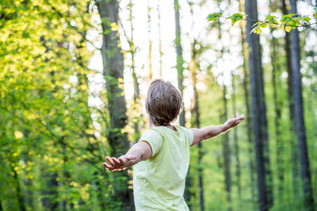 outspread: Young man celebrating nature standing in woodland with outspread arms facing the glowing morning sun through the trees. Stock Photo