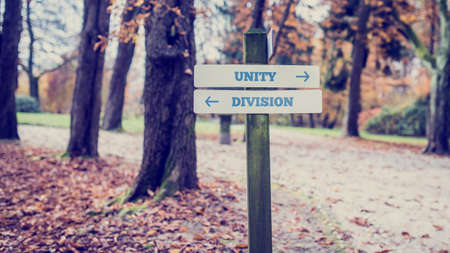 division: Signpost in a park or forested area with arrows pointing two opposite directions towards Unity and Division. Stock Photo
