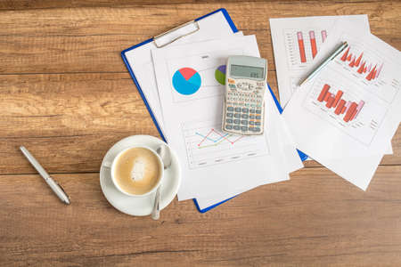 profit graph: Overhead view of paperwork and graphs spread out with a calculator and cup of coffee on a wooden business desk. Stock Photo