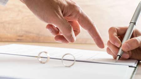divorcio: Mano apuntando macho a un documento de divorcio en la que una mujer está ocupado escribiendo con una pluma en una estrecha vista conceptual para arriba. Foto de archivo