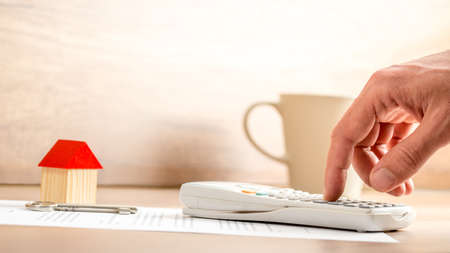 financial paperwork: Working out the costs of buying a house in a conceptual image of a person using a manual calculator on paperwork with a house key and small wooden model.