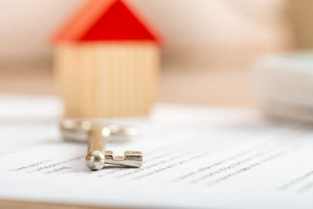 selling house: House key lying on a contract for purchase or insurance viewed low angle with focus to the tip. Stock Photo