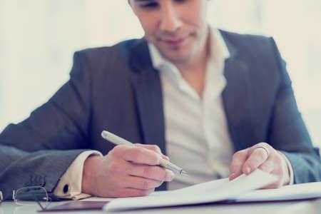 personas leyendo: Imagen retra del abogado de confianza joven u hombre de negocios a punto de firmar un contrato o acuerdo.