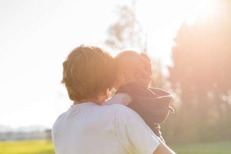 proteccion: Amar padre protector acunando su joven bebé en sus brazos en el cálido resplandor de la luz del sol.
