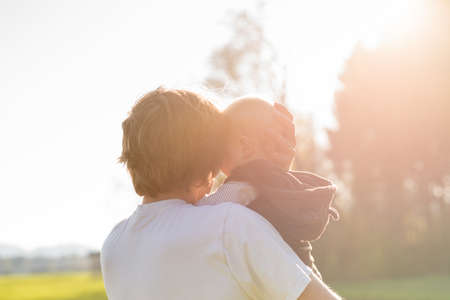 Loving protective father cradling his young baby in his arms in the warm glow of the sunlight.