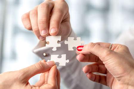 sinergia: Concepto de trabajo en equipo utilizando piezas de rompecabezas blancos bien coordinado por tres manos masculinas y femeninas en un concepto de desafío, de intercambio de ideas y la solución.