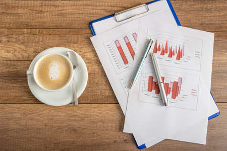 statistical: Top view of business statistical annual report of profit and income presented in graphs on a rustic wooden office desk with fresh cup of coffee. Stock Photo