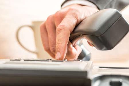 llamando: Primer plano de los dedos de un asesor de negocios de marcar fuera en un teléfono de línea terrestre presionando las teclas numéricas en el teclado en un concepto de comunicación. Foto de archivo