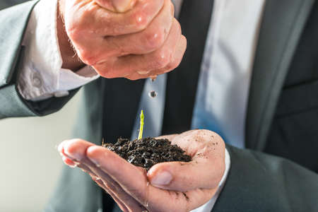 watered: Businessman pouring water over a small green plant growing in fertile soil held in his cupped left hand, concept of ecology, environment and eco-friendly business, close-up. Stock Photo