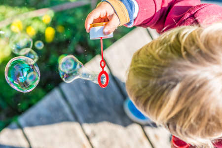 wooden deck: Overhead view of the top of the head of a young blond child blowing colorful iridescent bubbles with a soap solution while standing outdoors on a wooden deck in the garden.