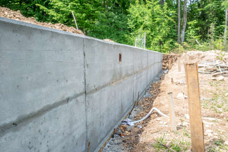 construction material: Long Cement Foundation Wall at Building Construction Site in Wooded Forest Area, Diminishing Perspective Leading Away from Camera. Stock Photo