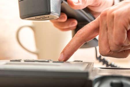 servicio al cliente: Close up Índice Dedo humano marcación en el teléfono Negro en la cima de la tabla con una taza de café en el lado.