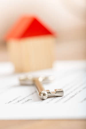 Silver house key lying on a contract for purchase, lease, insurance or mortgage in a real estate concept, viewed low angle with focus to the tip. Stock Photo