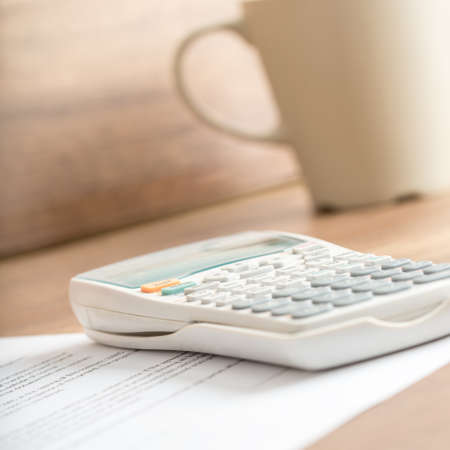 estimated: White plastic desk calculator for calculating the estimated costs written on a printed document next to a beige mug, on a wooden desk or workspace, close-up.