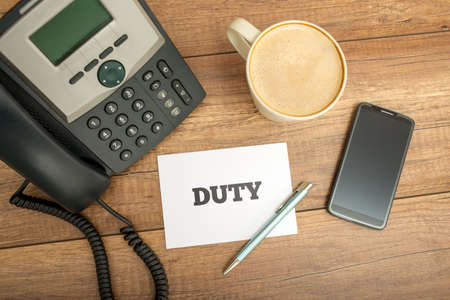 worktable: High Angle View of White Card with Duty Text on Top of Wooden Worktable with Telephone, Mobile Phone, Cup of Coffee and Pen.