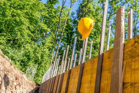 building foundation: Bright Yellow Hard Hat Hanging on Post of Unfinished Building Foundation Under Construction in Wooded Forest Area.