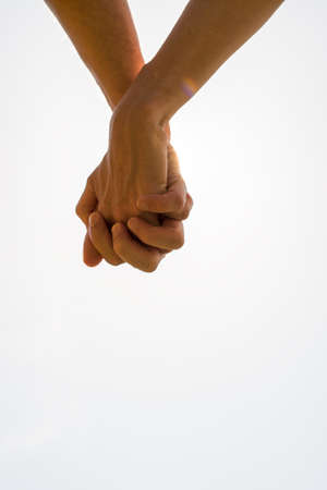 clasped hands: Couple with clasped hands in a closeup conceptual image of love and friendship with plenty of copyspace. Stock Photo
