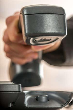 Close-up van een zakenman de hand opknoping up of een telefoongesprek op een klassieke zwarte vaste telefoon beantwoorden.