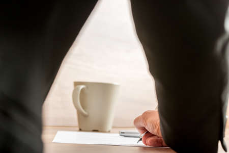 body writing: Businessman writing on a document with a mug of coffee standing on the desk, low angle view between his arm and body of the paperwork. Stock Photo