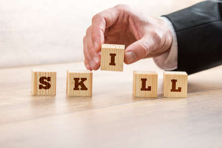 leading education: Close up Businessman Hand Arranging Wooden Blocks on Top of the Table to Form Skill Word.