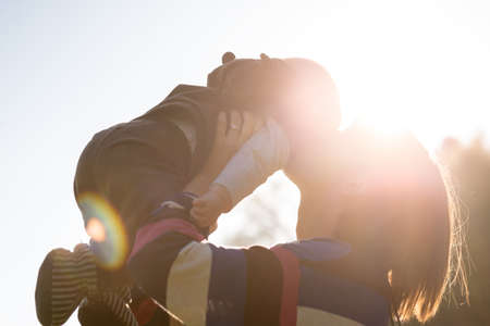 convivencia familiar: Elevación de la mujer y la besa al bebé retroiluminada por la luz del sol brillante al aire libre en la familia, el amor y la unión con temas imagen.