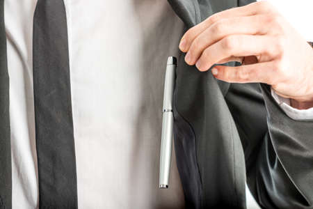 breast pocket: Businessman lifting aside his jacket by the lapel in order to access a pen in an inner pocket of the jacket or breast pocket of his shirt, close up view of his hand and chest.