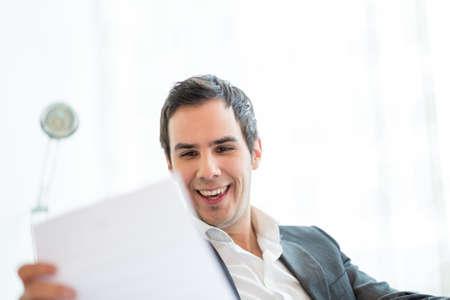 documentos: Cierre de negocios feliz joven que se sienta en su escritorio, Lectura Buena Nueva en el documento en su mano. Foto de archivo