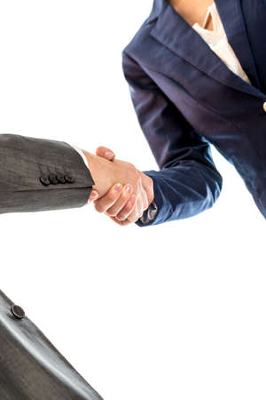 deal in: Businesspeople shaking hands to close a business deal, in partnership, teamwork or trust, isolated on white background. Stock Photo