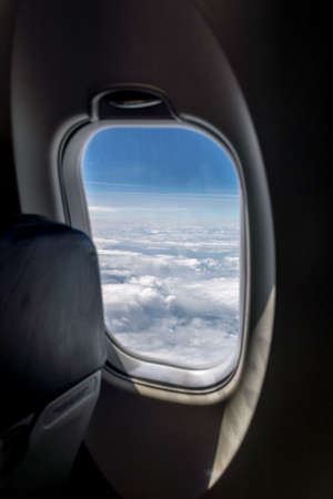 altitude: Aerial view seen through the round small window of a commercial airplane flying at high altitude above the clouds.