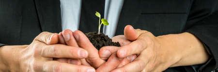 男と女の新しい植物カッピングを育成概念イメージで手に豊かな肥沃な土壌で若い発芽苗は絡んだカップ手のビューを閉じます。