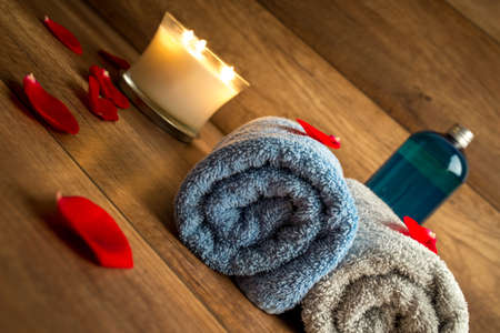 sensual massage: Romantic Spa Still Life Concept with Two Rolled Towels, Lit Candle and Bottle of Massage Oil Surrounded by Red Rose Petals with Wooden Background. Stock Photo