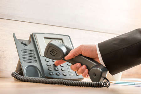 Closeup of a hand in a formal elegant suit dialing a telephone number on a classical black landline phone. Conceptual of global business communication and telemarketing.