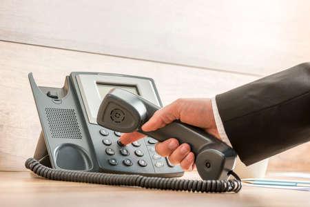Primer plano de una mano en un elegante traje formal de la marcación de un número de teléfono en un teléfono fijo negro clásico. Conceptual de la comunicación global de negocios y telemarketing. Foto de archivo
