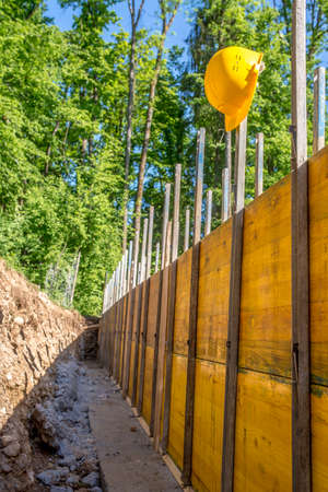 building foundation: Construction Site Concept with a Bright Yellow Hard Hat Hanging on Post of Unfinished Building Foundation Under Construction in Wooded Forest Area. Stock Photo