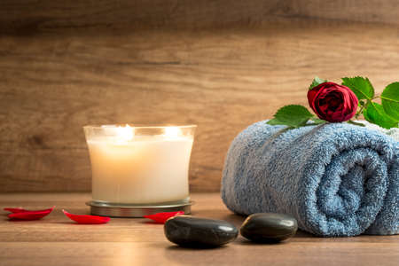 spirituality therapy: Romantic spa arrangement with a burning white scented candle, red petals, two black stones and a rose on a blue folded soft towel.