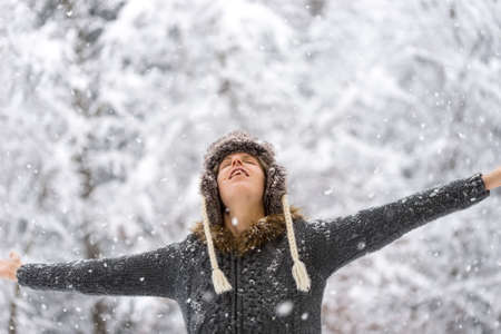 outspread: Woman standing outdoors in falling snow with her arms outspread and head tilted back with closed eyes.
