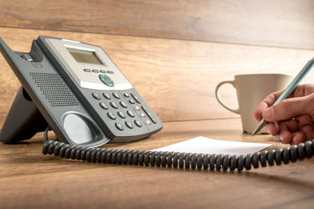 aide à la personne: Gros plan de la main des hommes prenant des notes importantes comme il répond à un appel sur un téléphone fixe classique. Concept de l'assistance et le secrétaire travail.