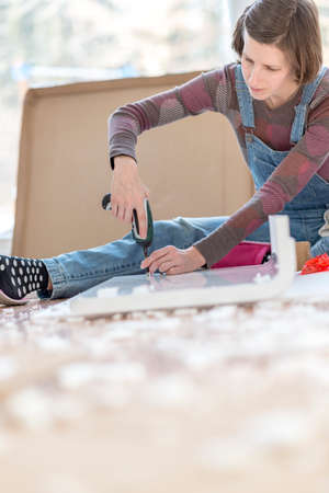 Competent young woman assembling flat pack furniture using a handheld drill as she braces it with her leg for stability.